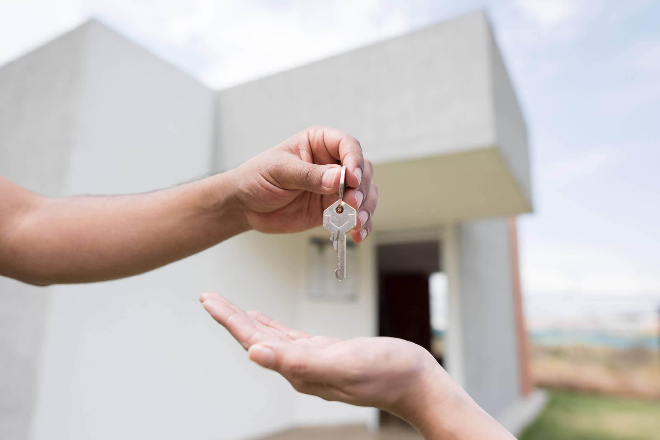 Uma mão entregando chave numa outra mão com uma casa branca ao fundo