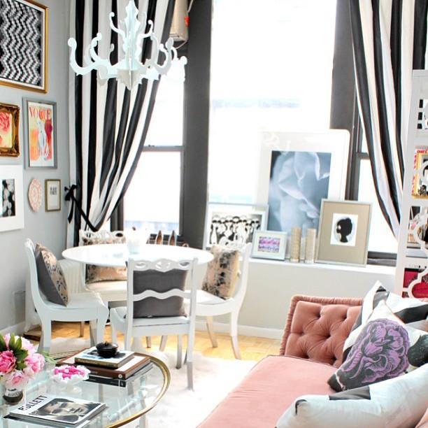 Sala com cortinas listradas preto e branco ao fundo, uma mesa de jantar branca pequena com cadeiras clássicas, um sofá rosa claro, uma mesa de centro oval de vidro com artigos de decoração e vários quadro sobre a parede à esquerda