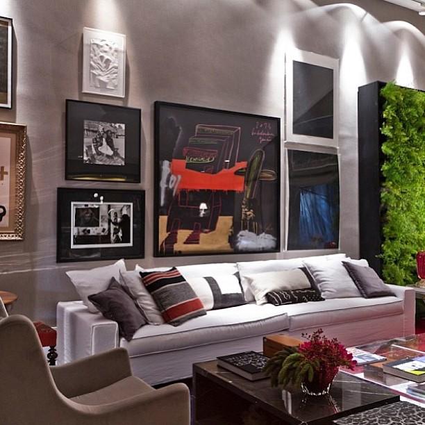 Sala de estar com com quadros e pôsteres na parede, um sofá cinza com almofadas, uma poltrona bege no canto esquerdo e uma mesa de centro
