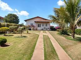 Chácara com área verde e um caminho asfaltado para uma casinha branca ao fundo
