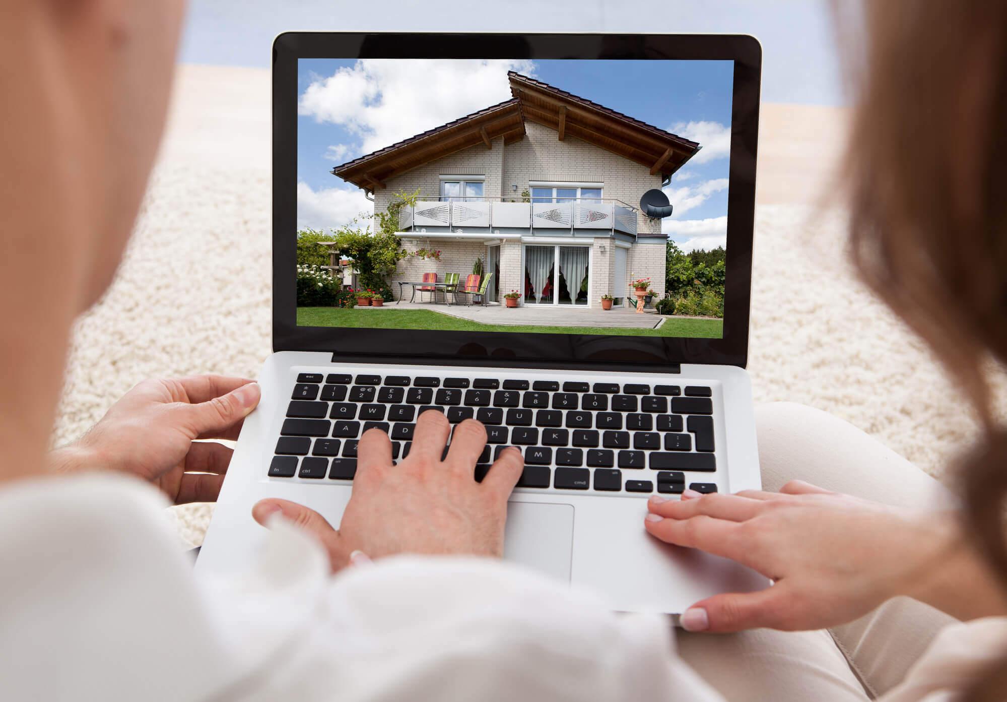 Casal com notebook aberto olhando a foto de uma casa de dois andares com um gramado à frente na tela do computador
