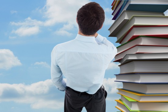 Thoughtful businessman with hand on chin against pile of books against sky