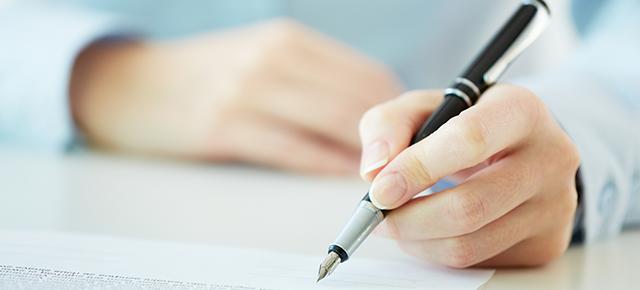 Mão esquerda de pessoa branca, segurando uma caneta e assinando um documento sobre uma mesa de madeira clara