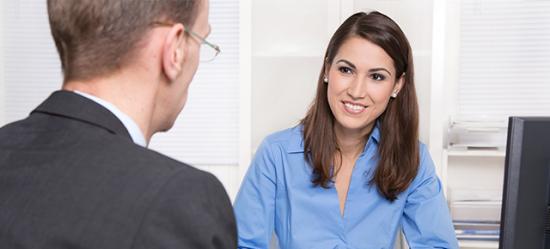 Homem, de costas na foto, e mulher conversando, sentados ao redor de uma mesa de escritório com um computador a frente dela