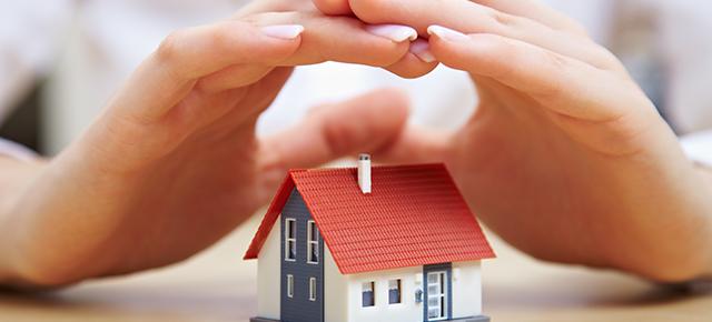 Duas mãos unidas sobre uma casa em miniatura, que está em cima de uma mesa