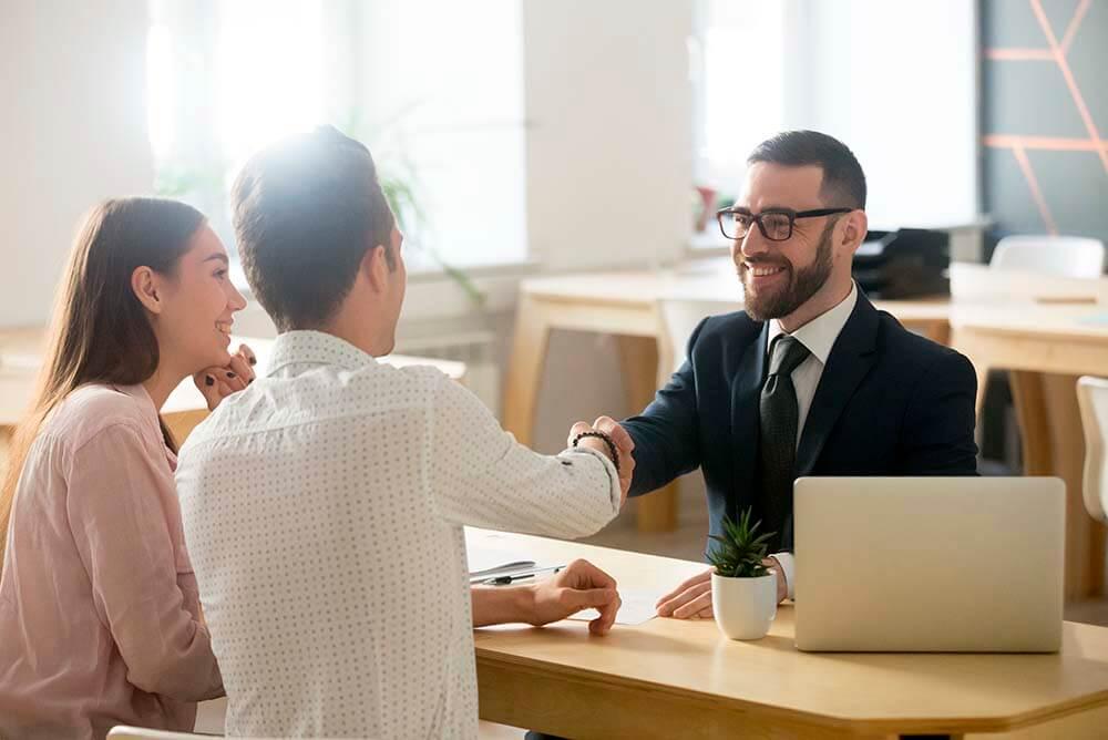 Casal sentado numa mesa de madeira, mulher de blusa rosa, homem de blusa branca, ambos sentados de frente para um homem, de terno preto, numa mesa. O homem tem um computador a sua frente e cumprimenta o homem do casal