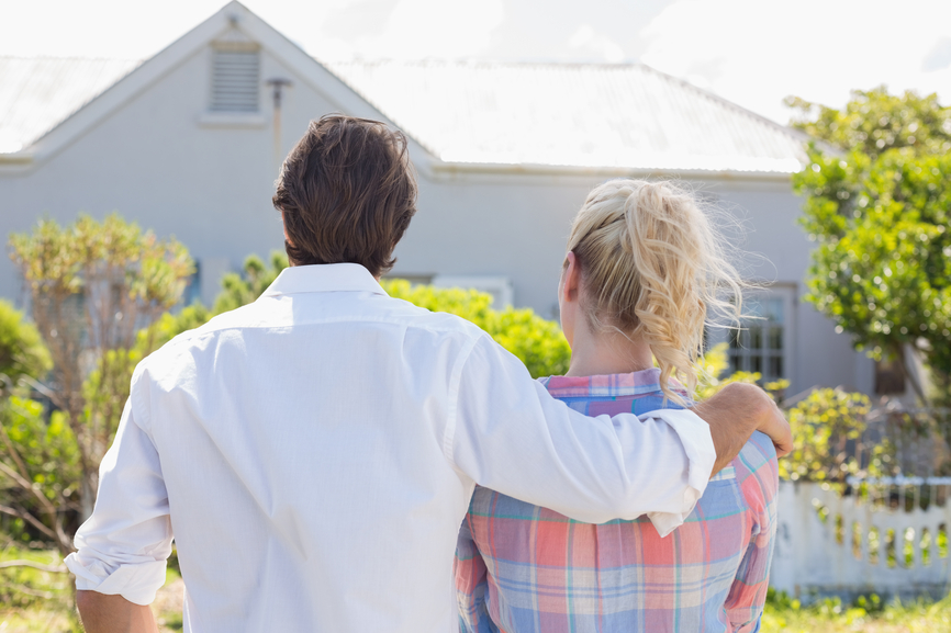 Cute couple standing together in their garden looking at house on a sunny day