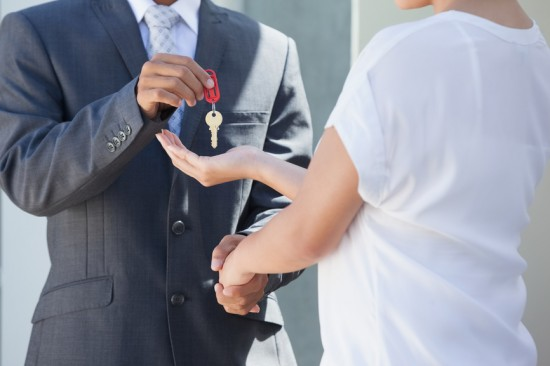 Estate agent giving house key to buyer outside a house