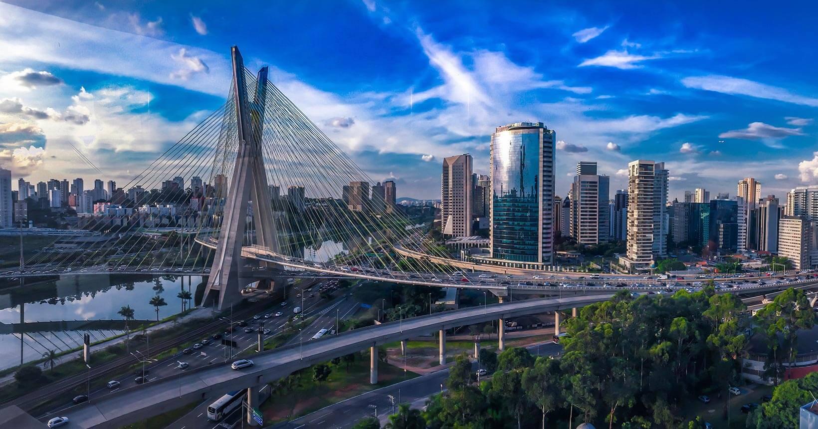Imagem aérea de São Paulo, em dia de céu azul, na qual se vê prédios, a ponte estaiada e parte do rio Tietê