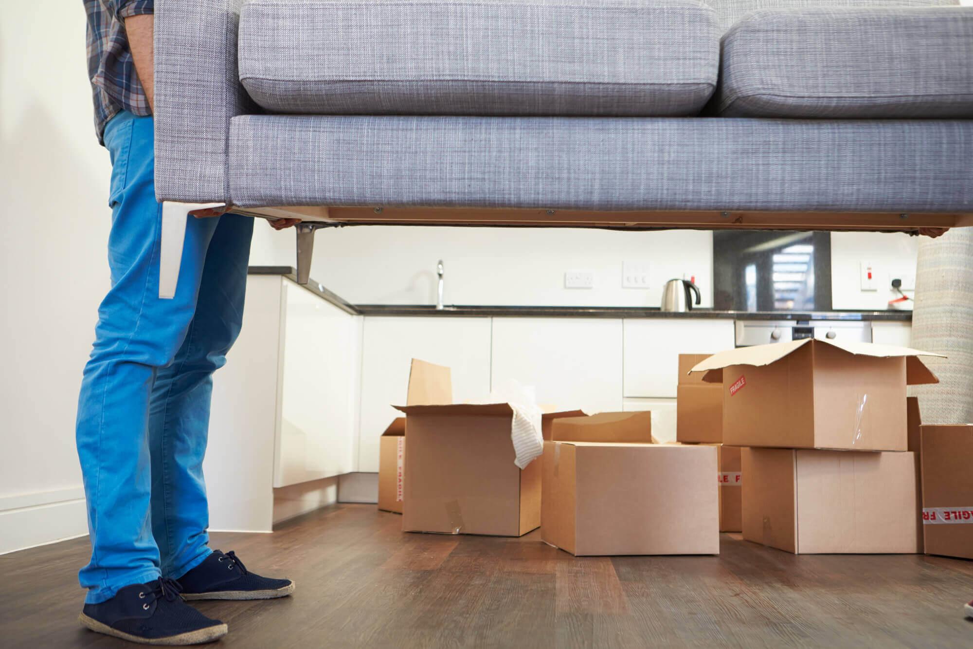 Homem de calça jeans carregando um sofá cinza e, ao fundo, caixas empilhadas