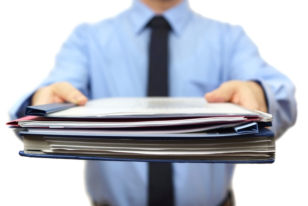 Homem, o qual não se vê o rosto, de camisa social azul e gravata preta, segurando uma pasta de documentos com os braços estendidos para frente