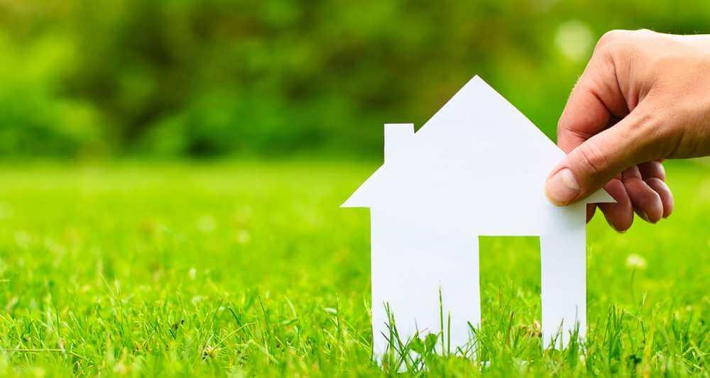Foto de um gramado ao fundo com uma mão segurando a miniatura de uma casinha de isopor em primeiro plano