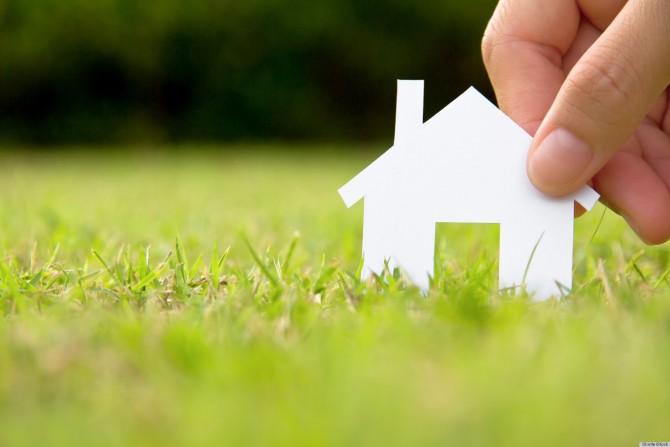 Mão segurando uma casa branca em miniatura sobre um gramado