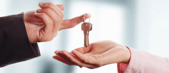 Uma mão masculina, passando uma chave para uma mão feminina