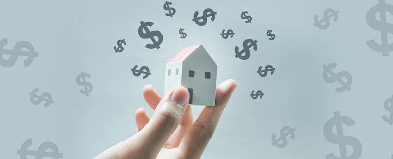 Mão segurando uma casa branca em miniatura com vários símbolos de dólar ao redor
