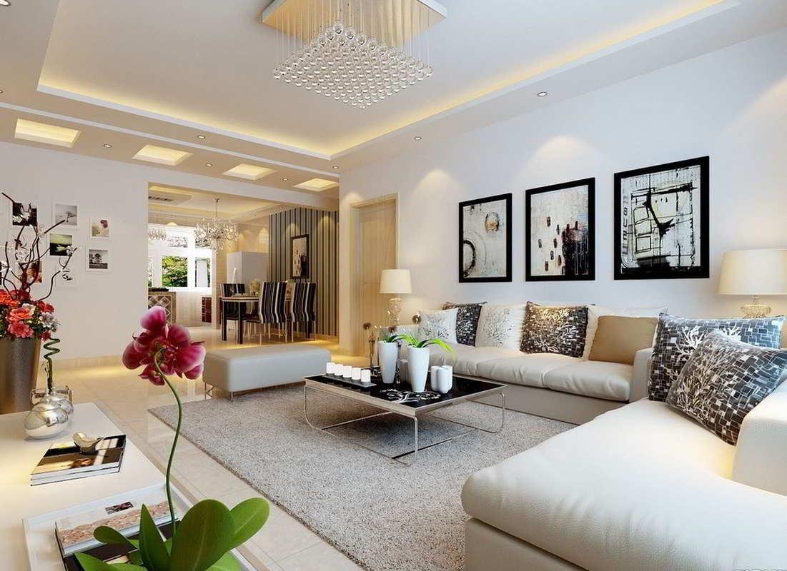 Sala de estar de um apartamento, com um sofá branco em L, com diversas almofadas, uma mesa de centro e uma sala de jantar ao fundo.