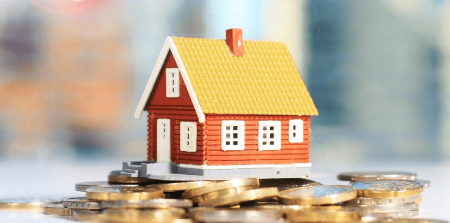 Casa em miniatura em cima de várias moedas espalhadas sobre uma mesa