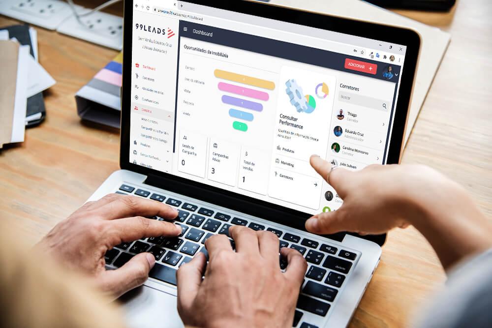 Notebook aberto com mãos sobre o teclado e uma mão de outra pessoa apontando para a tela em que se vê uma planilha