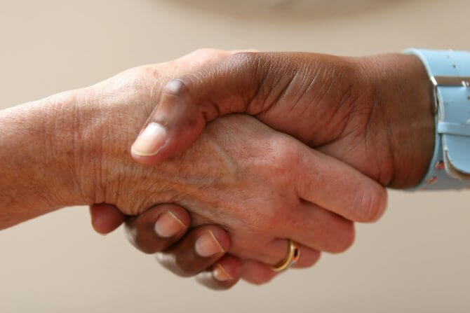 Duas mãos entrelaçadas, aparentemente se cumprimentando ou fechando um acordo. Uma de uma pessoa branca, à esquerda, e outra de uma pessoa negra, à direita.