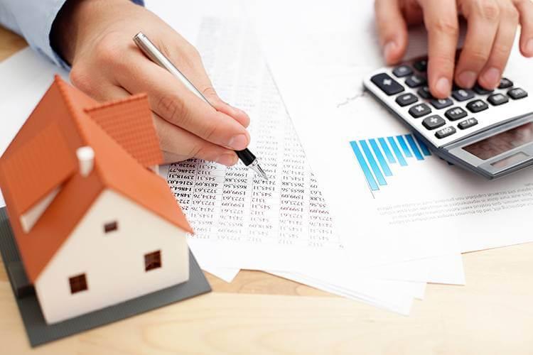 Mãos de uma pessoa anotando coisas em folhas sobre uma mesa. A caneta na mão direita e uma calculadora na mão esquerda. Há ainda uma casa em miniatura em primeiro plano, à esquerda.