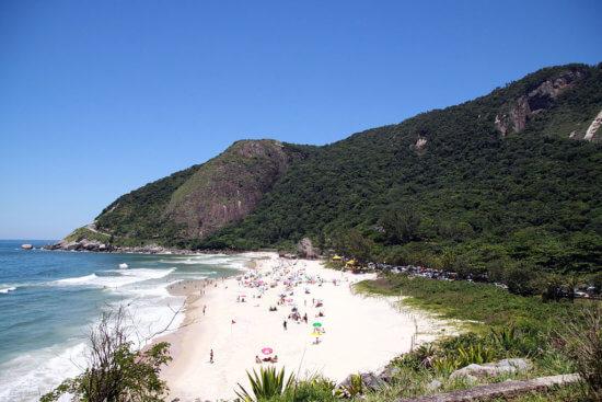 Foto área de uma praia, com morro ao fundo, faixa de areia e um pedaço do mar. Sobre a areia alguns banhistas.