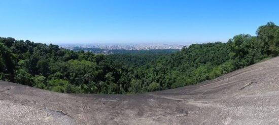 Vista aérea da Pedra Grande. Com árvores em frente e prédios do Rio de Janeiro ao fundo.