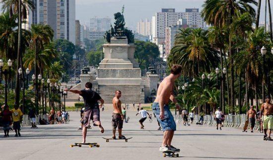 Homens andando de skate em frente a estátua do parque, com coqueiros de um lado e do outro
