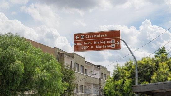 Uma placa de dor vinho, suspensa, com árvores ao redor e um prédio antigo ao fundo, indicando a direção da Cinemateca da Vila Mariana