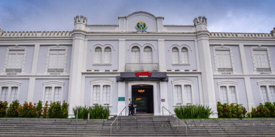 Fachada de um prédio branco clássico, de dois andares, com uma escadaria a frente