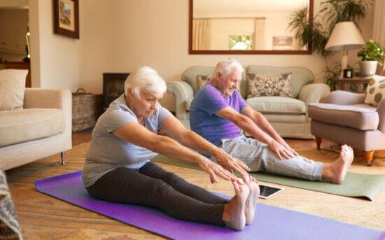 Casal de idosos se exercitando em casa.