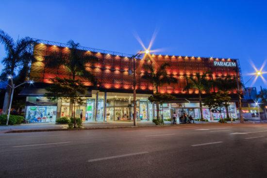 Fachada do shopping Buritis, com coqueiros a frente, lojas no térreo e luzes alaranjadas por todo o vidro preto no segundo pavimento.