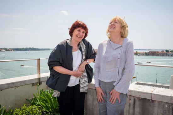 Duas mulheres sorrindo, próximas ao parapeito de uma passarela, onde atrás se vê um rio com alguns barcos