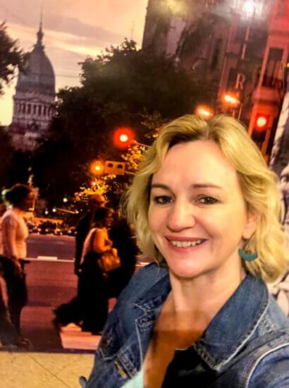 Descrição da imagem: Em primeiro plano há uma mulher, loira, sorrindo. Em segundo plano, pessoas caminhando em uma rua movimentada.