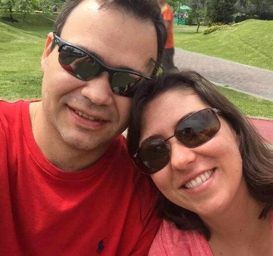 Thais e seu marido sorridentes, em primeiro plano, ambos de óculos escuros, posando para uma self com um parque ao fundo.