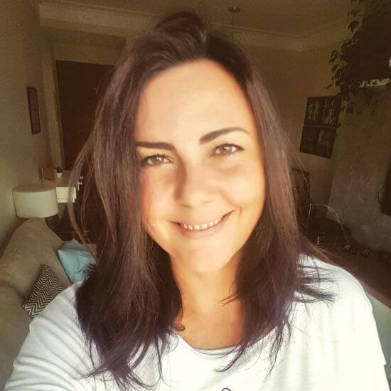 Descrição da imagem: Em primeiro plano, uma mulher, morena, usando blusa branca, faz uma selfie. No fundo, um sofá e uma sala de estar.