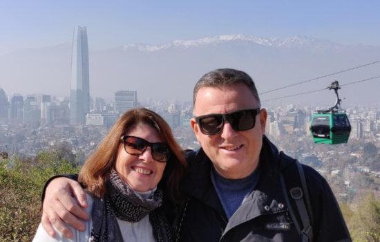 Uma mulher e um homem sorridentes, abraçados, de óculos escuros em primeiro plano. Ao fundo, um bondinho e a vista aérea dos prédios de uma cidade.