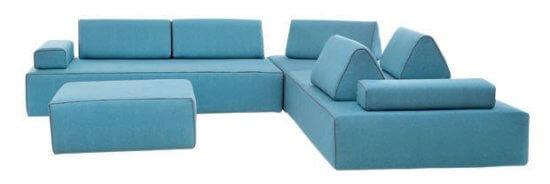 Sofá de linho azul, em formato de L, feito em módulos que se separam.