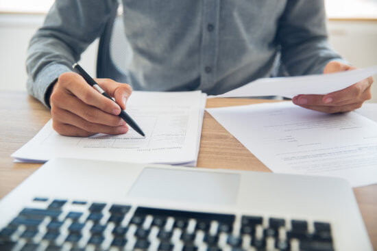 Homem analisando documentos em frente ao computador.