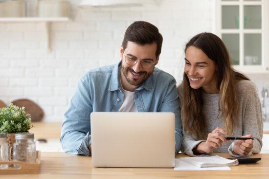 Casal sorrindo em frente ao computador
